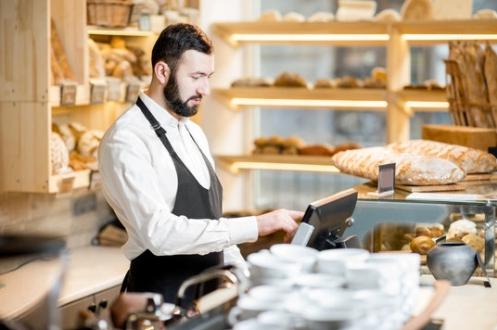 boulanger devant une caisse  enregistreuse tactile