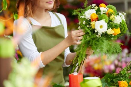 fleuriste qui confectionne un bouquet